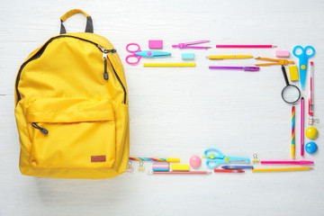 Frame made of backpack with school supplies on white wooden background