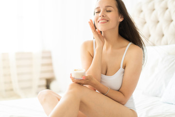 Pretty brunette using body cream on bed at home. Wall mural