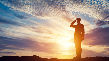 Soldier saluting at sunset. Army, salute, patriotic concept.