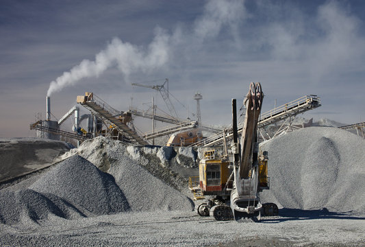 Excavator and large heaps of gravel on the background of smoke from the pipe of the rock stone crushing plant. Mining industry. Quarry mining equipment.