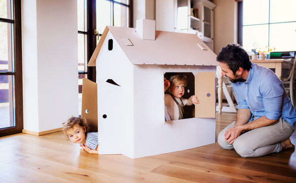 Two toddler children with father playing with paper house indoors at home.