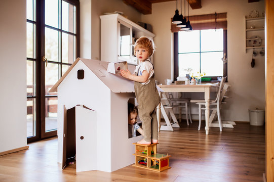 Two toddler children playing with a carton paper house indoors at home.