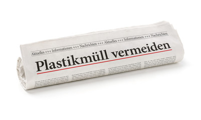 Zeitungsrolle mit der Überschrift Plastikmüll vermeiden