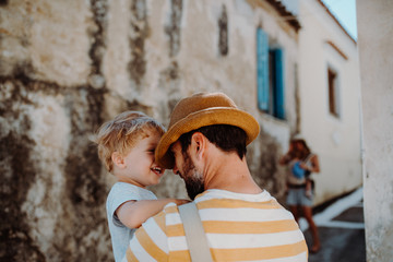 A father holding a toddler son in town on summer holiday.