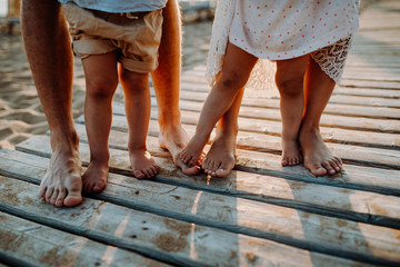 Legs and feet of family standing on beach on summer holiday, a midsection.