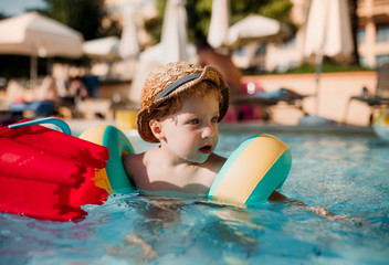 A small toddler boy with armband swimming in water on summer holiday.