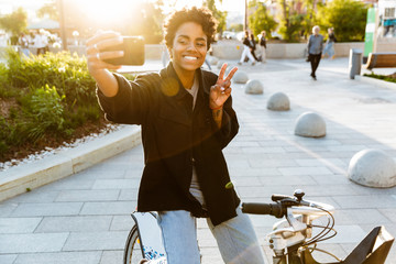 Photo of happy african american woman taking selfie on cellphone while sitting on bicycle in city park