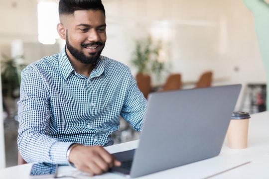 Indian entrepreneur working on laptop in modern office