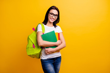 Close up photo amazing she her lady hold arms hands school colored notebooks last year studying cool modern backpack wear specs casual white t-shirt jeans denim isolated bright yellow background