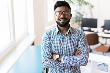 Portrait of smiling Indian man crossed arms standing at modern office