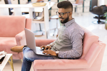Casual young indian man using laptop with happy on sofa in modern office