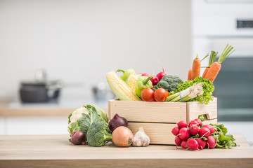 Wooden box full of fresh healthy vegetables. Broccoli carrot radish onion garlic corn on wooden kitchen table Wall mural