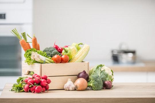 Wooden box full of fresh healthy vegetables. Broccoli carrot radish onion garlic corn on wooden kitchen table
