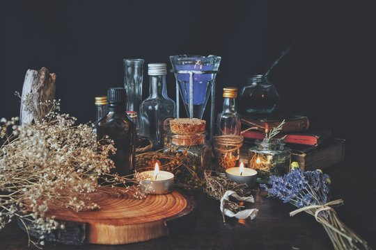 Wiccan witch apothecary - various ingredients, potions and dried herb bottles, jars for magick, placed on an altar. Dark, black background with baby's breath flowers, lavender, burning candles, books
