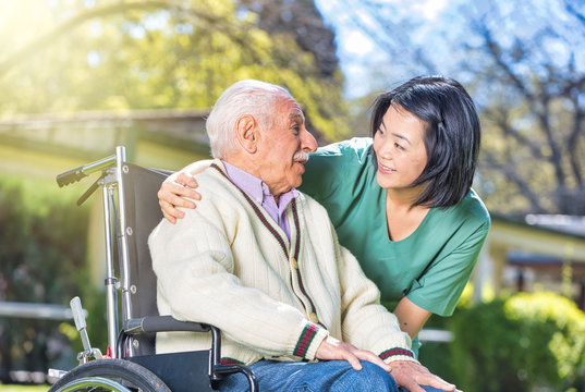 Senior retired man in the garden with their caregiver
