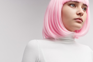 Female robot in pink wig looking away