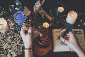 A witch casting a spell and writing it down in her Book of Shadows with a green black feather and ink. Wiccan witch altar filled with nature objects branches dried flowers herbs burning candles potion