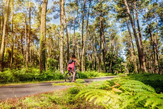 femme se promenant en vélo dans la forêt des Landes