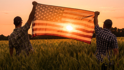 Photo sur Toile Orange eclat Two men energetically raised the US flag in a picturesque field of wheat