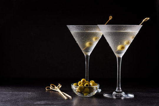 Classic Dry Martini with olives on black background. Copyspace