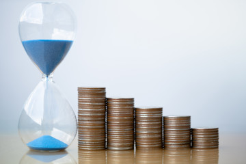 Hourglass blue sand and stack of coins. Business investment growth concept. money saving and Investment. Risk management. Time is money. Time investment and retirement saving. 401K.