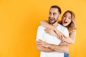 Image of impressed couple man and woman expressing wonder while looking aside at copyspace