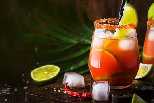 Michelada - Mexican alcoholic cocktail with beer, lime juice, tomato juice, spicy sauce and spices, vintage wooden background, selective focus
