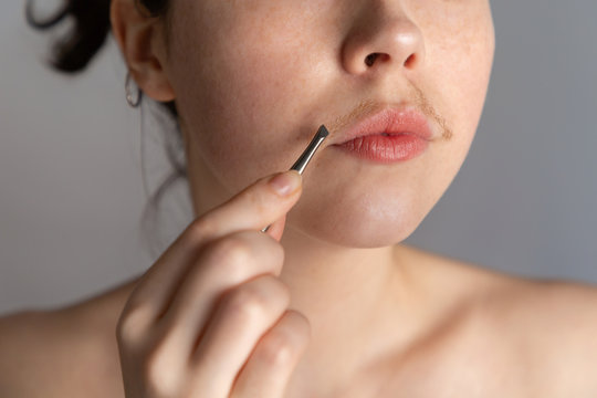 A young woman with a mustache tries to remove the hair over her lip with tweezers. The concept of getting rid of unwanted facial hair. Close up