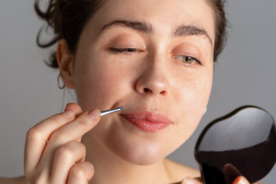 A young woman looks in the mirror and plucks her hair over her upper lip with tweezers. The concept of getting rid of unwanted facial hair. Close up