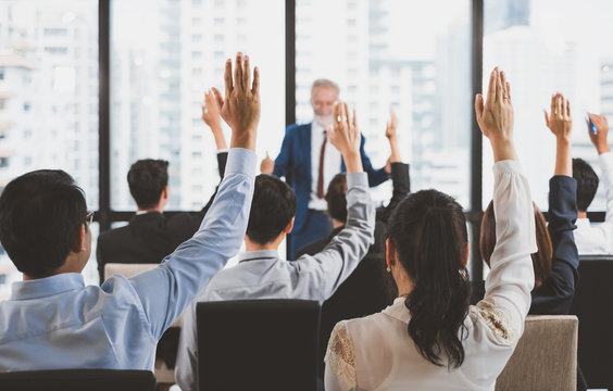 Group of business people raise hands up to ask question and answer to speaker in the meeting room seminar