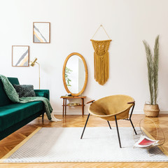 Stylish and elegant interior of living room with design gold armchair, velvet sofa, lamp, poster frames. dressing table with mirror, plants, palm leaves, yellow macrame and accessories. Home decor.
