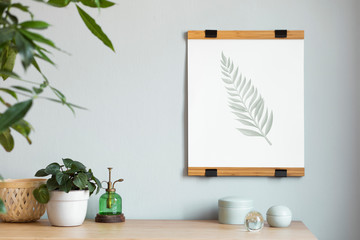 Stylish scandinavian interior with design wooden table, brown mock up photo frame ,beautiful plants in design pots and nice accessories. Modern home decor. Gray background wall. Minimalistic concept.