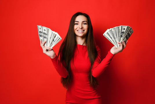 Young pretty woman in red dress hiding behind bunch of money banknotes