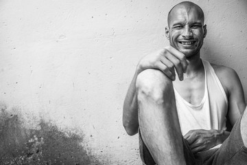 Canvas Prints Bar Young skinny anorexic bald positive and happy smiling homeless man sitting on the urban street in the city or town near white wall with big smile, homelessness social documentary concept