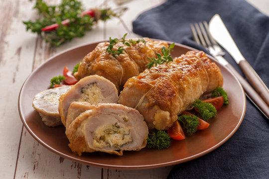 Stuffed chicken roll s vegetable garnish and herbs.