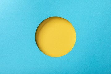 blue paper background with minimalistic yellow round hole Wall mural