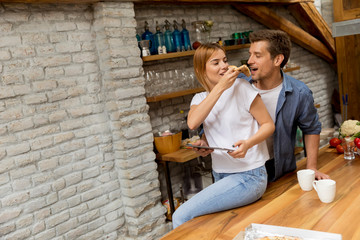 Young couple eating pizza and using digital tablet by the table in the rustic apartment