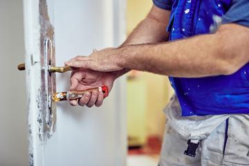 Handyman using chisel around doors lock tto scrub the old paint.