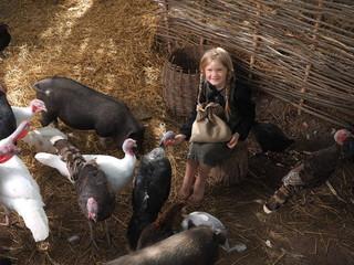 Village girl sitting among farm animals. Portrait of child