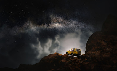 Four by four off road car crossing through the country road against the milky way and stars in the night. (Elements of this image furnished by NASA)