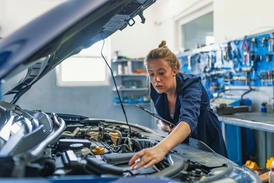 Mechanic working under the hood at the repair garage. Portrait of a happy mechanic woman working on a car in an auto repair shop. Female mechanic working on car