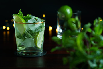 Poster de jardin Cocktail Mojito served in a glass with gold rim. Limes and mint in bokeh, dark wooden table, high resolution