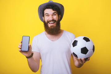 Excited bearded man looking at the camera holding a soccer ball and his smartphone.