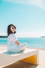 woman sitting at sun lounger at sea beach in white clothes. summer vacation concept