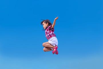 青空をバックにジャンプする幼い女の子。元気、パワフル、健康イメージ