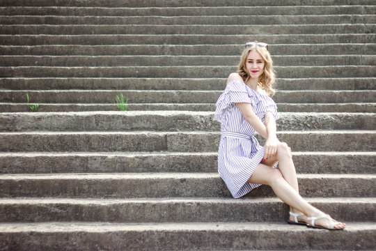 Blonde in white dress on stairs