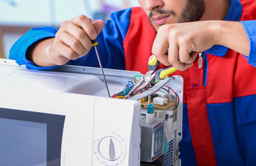 Obraz Young repairman fixing and repairing microwave oven - fototapety do salonu