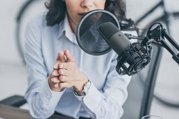 cropped shot of radio host speaking in microphone in broadcasitng studio