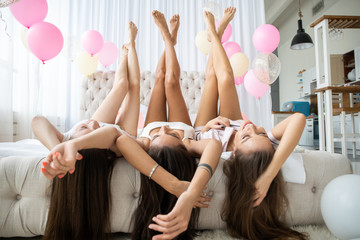 Charming pretty cheerful foolish attractive sexy stylish slender girls lying head over heels on bed with raised crossed legs hands celebrating birthday holiday event looking at camera sleepover party.