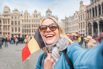 Woman tourist stands with the flag of Belgium on the background of the Grand-Place or the Grand Market Square in Brussels Wall mural